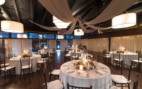 a reception dining area at night with circular tables draped in white tablecloths, black chairs, and white lantern centerpieces