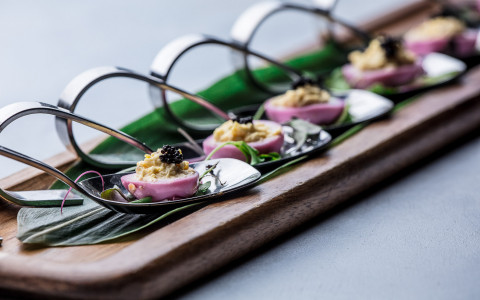 elegant small pink appetizers on black spoons on a wooden serving tray
