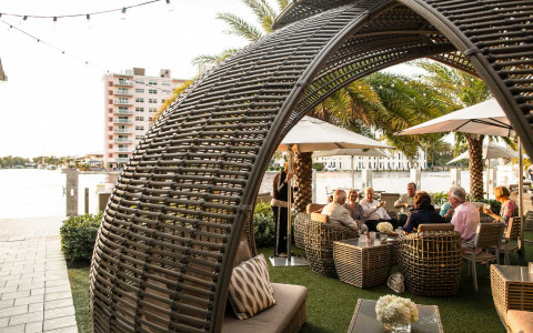 outdoor grass patio area with a large wicker covered couch area and table seating along the water