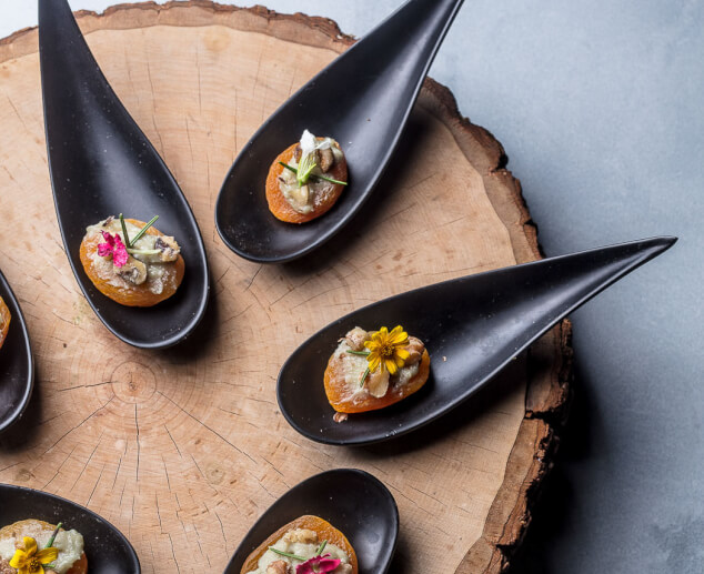 individual crackers with toppings on black teardrop spoons on a rustic wooden tray