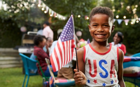 child holding flag at fourth of july bbq
