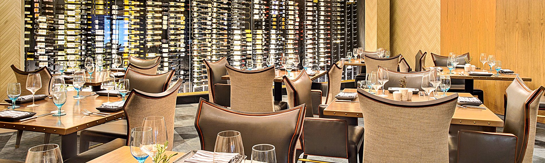 Restaurant dining tables set with a large wine cellar on the back wall
