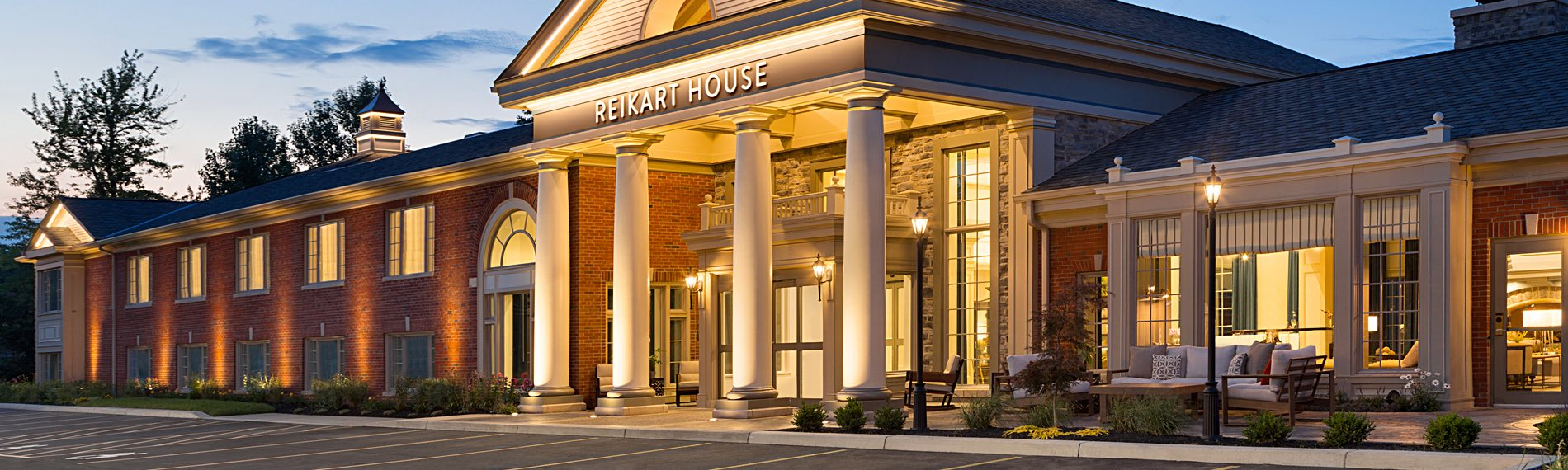 Exterior of the Reikart House building with 4 large columns at entrance lit up at night