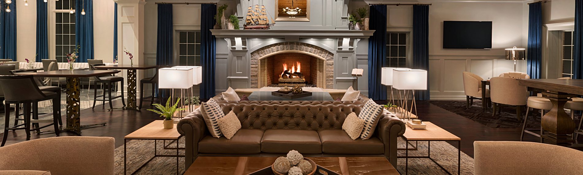 Comfortable lounge area with a brown leather couch, fireplace and hightop table and chairs