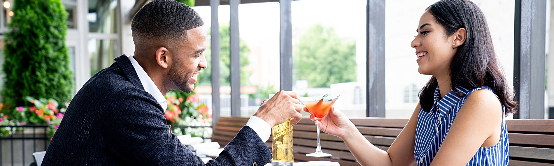 Two people sitting at a restaurant holding a beer and a cocktail