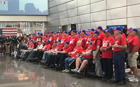 A group of veterans gathered together wearing matching red shirts and blue hats