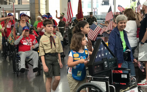 A group of boy scouts and girl scouts helping the elderly