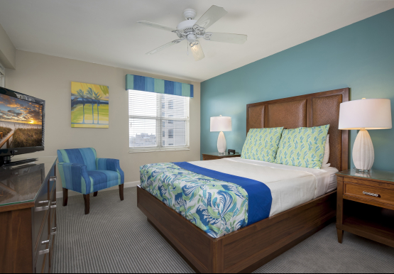 Room with king bed, blue accent decor, wooden furniture & window