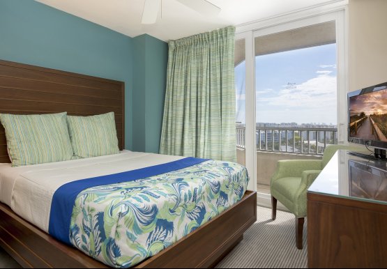 Room with queen bed, wooden dresser with tv & balcony