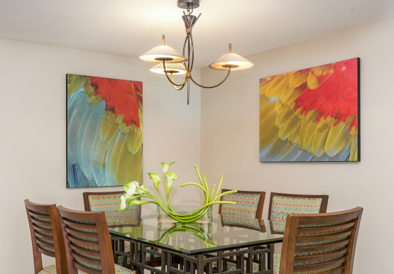 Dining area with table, six chairs & tropical paintings on wall
