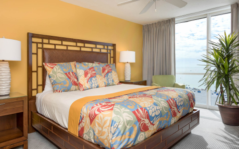 King bedroom with tropical patterned bedding, wooden furniture & beach view window