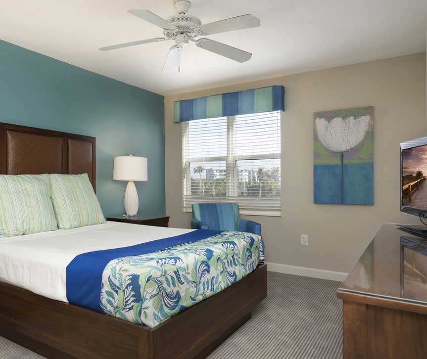 Room with queen bed, wooden dresser with tv, blue accent decor & window