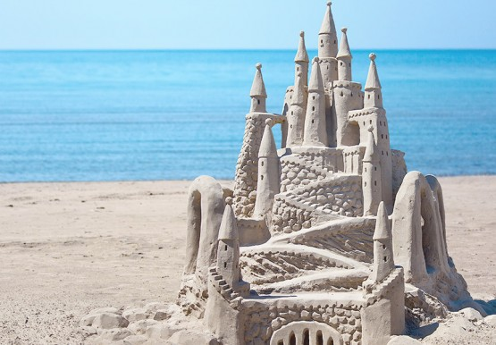 Big & detailed sand castle beside the ocean water
