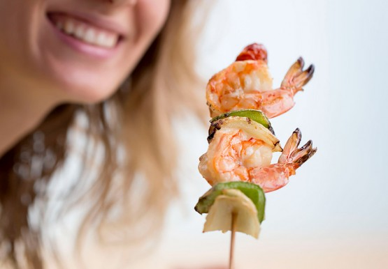 Woman holding wooden skewer with shrimp, onion & pepper