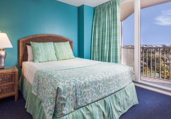 Room with double bed, brown wicker nightstand, teal wall & balcony curtain open