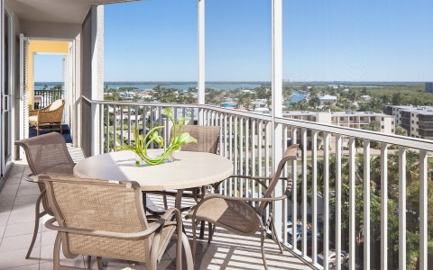 Table with chairs on room balcony overlooking island