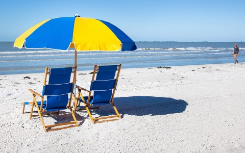 Blue beach chairs with striped yellow & blue umbrella on sand facing ocean