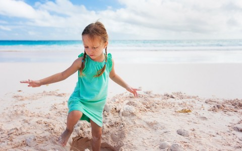 Little girl playing in the sand with ocean in the back