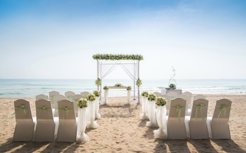 Rows of chairs wrapped in sheer white fabric in front of wedding arc on beach