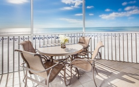 Table with chairs on balcony overlooking ocean