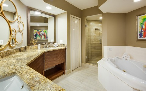 Full bathroom with granite countertop, vanity, shower & white tub