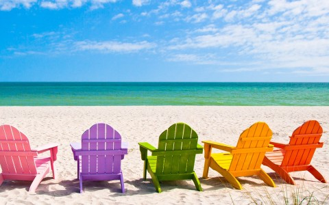 Colorful beach chairs lined up on sand with ocean in the back