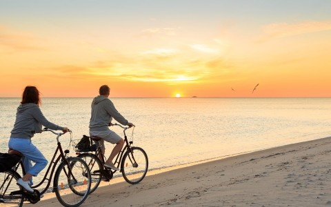 Couple riding their bikes on sand by the water during the sunset