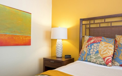 Close up of bed with tropical print comforter & wooden nightstand