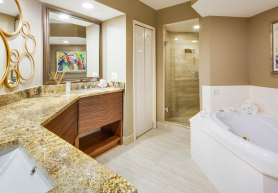 Large bathroom with double sinks, granite countertops, shower and a bath tub