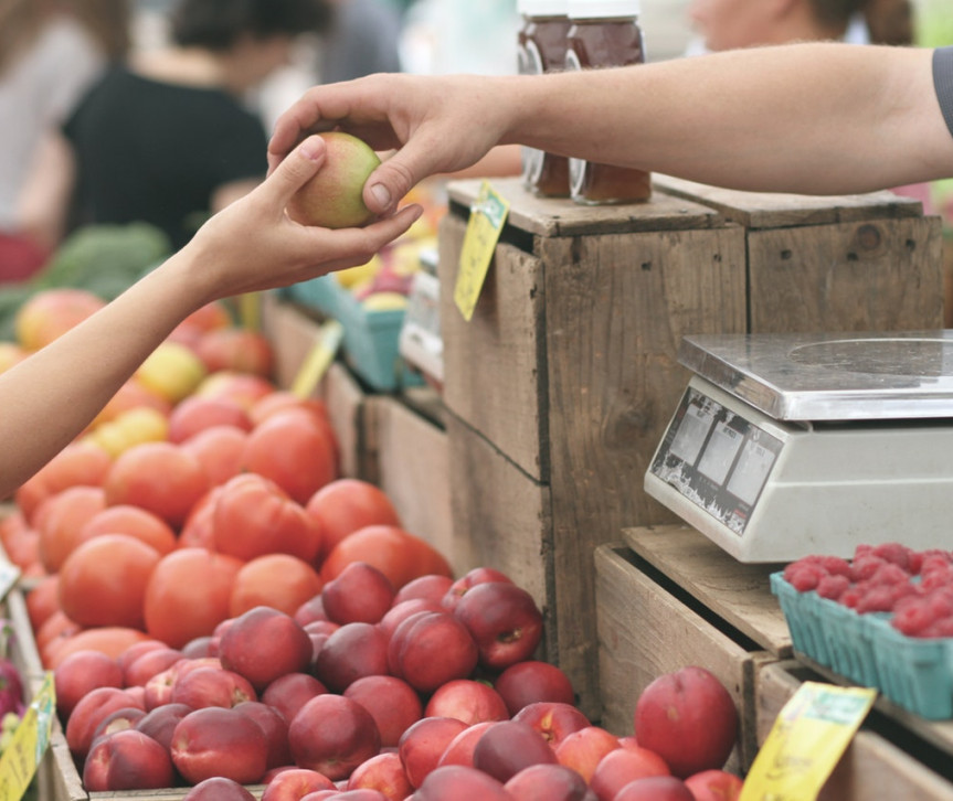 a person buys fruit at farmers market
