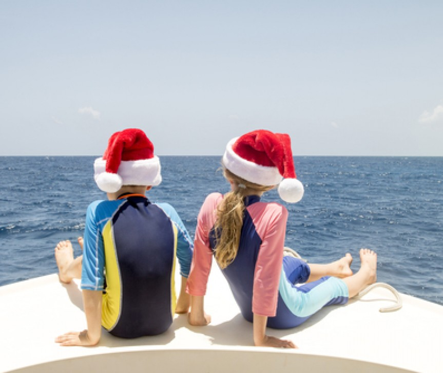 two kids on the bow of a boat wearing santa hats