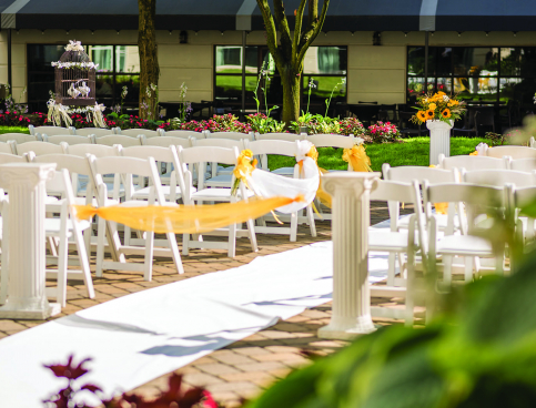 Outdoor wedding set with rows of white chairs & small white columns on either side of aisle