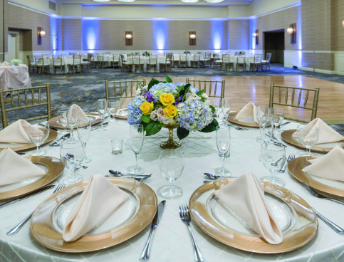 Close up of table with gold charger plates & beige napkins