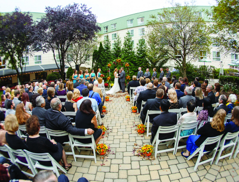 Guests seated on white chairs of outdoor wedding with couple under arc