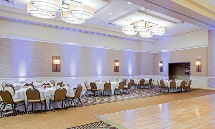 Large room with round tables set for reception next to wooden dancefloor