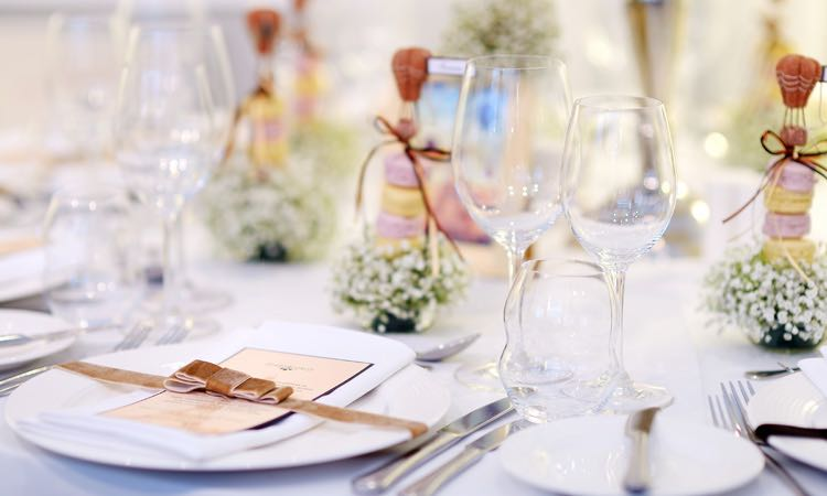 Close up of white dinnerware next to wine glasses set for wedding