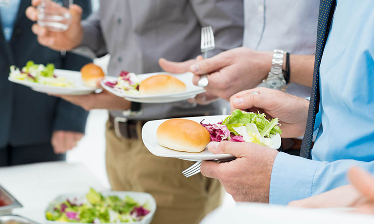 Close up people holding small plates with salad & bread
