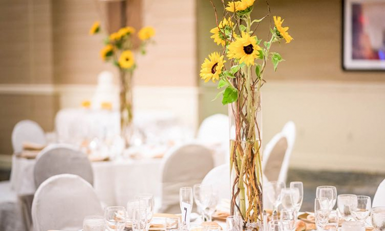 Small sunflower arrangement on tables for reception