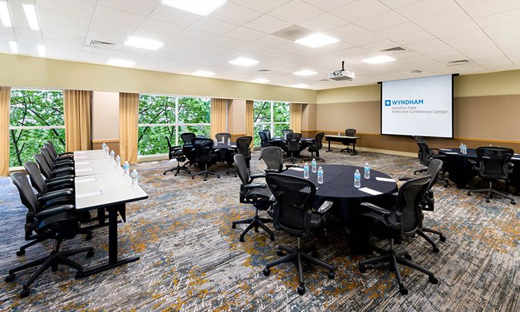 Boardroom with one long rectangular table & other circular tables facing projection screen