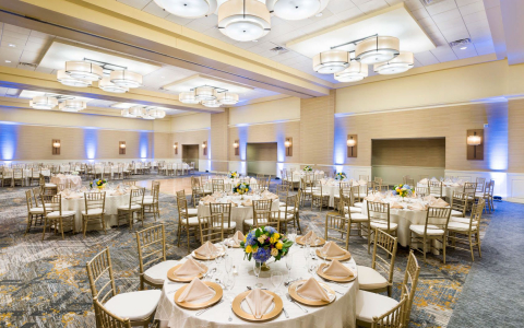 Room with round tables set for reception with white tablecloths & gold accented chairs