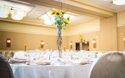 Table set for reception with sunflower centerpiece arrangement