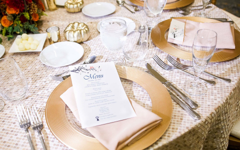 Table set for wedding reception with invitation on gold plate