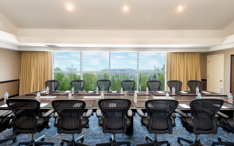 Room with long rectangular table & chairs set for meeting next to large window