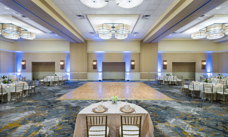 Large event space with round tables set for reception next to wooden dance floor