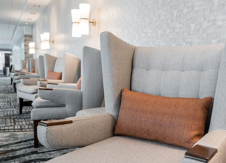 Lobby area with grey sofa chairs& patterned carpet