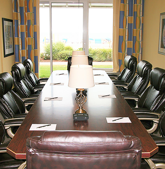 meeting room with dark wood long table and leather chairs with a big window