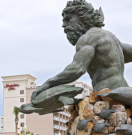 statue of Poseidon with the hotel in the background