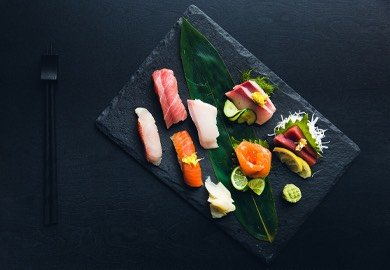 Colorful sushi prepared on a black plate and tabletop