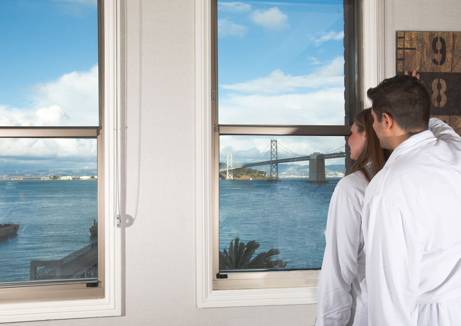 Couple in robes looking out the window at the San Francisco Bay