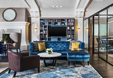 Sitting area with blue velvet sofa and yellow accent pillows